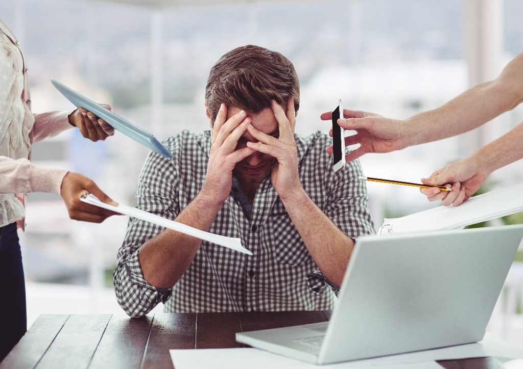 a man with stress frustrated with electronic devices in office